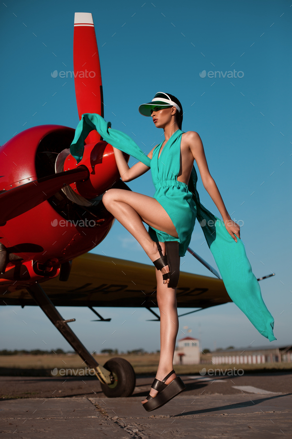 Beautiful fashion model girl in a visor posing next to propeller plane at runway during sunset - Stock Photo - Images