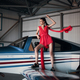 Fashion photo of model girl in a red dress standing on the wing of a propeller plane in the garage - PhotoDune Item for Sale