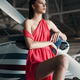 Beautiful fashion model pilot girl in a red dress posing next to propeller plane in the garage - PhotoDune Item for Sale