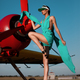Beautiful fashion model girl in a visor posing next to propeller plane at runway during sunset - PhotoDune Item for Sale