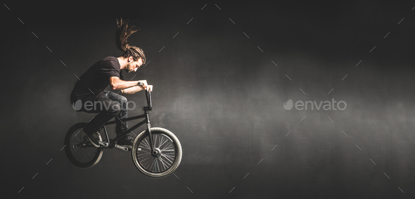 Young man jumping on BMX bicycle - Stock Photo - Images