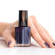 Hand of a woman with dark manicure and nail polish bottle on white background - PhotoDune Item for Sale