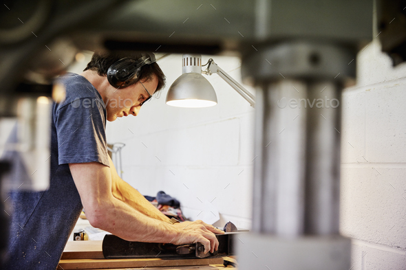 Man using a lathe to smooth wood - Stock Photo - Images
