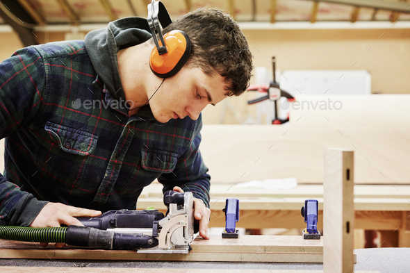 A young man using tools to shape a piece of wood in a  furniture workshop. - Stock Photo - Images