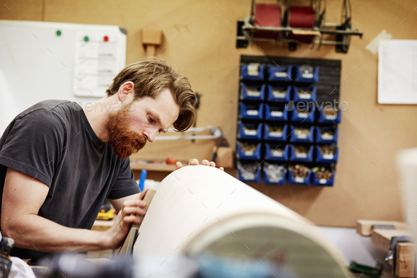 A man in furniture workshop working on a curved wooden piece of furniture. - Stock Photo - Images