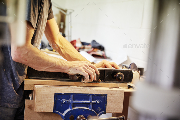 A man holding a piece of wood in a furniture workshop making bespoke contemporary furniture. - Stock Photo - Images