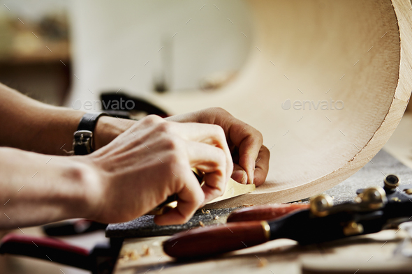 A man in a furniture workshop working on a piece of curved wood. - Stock Photo - Images