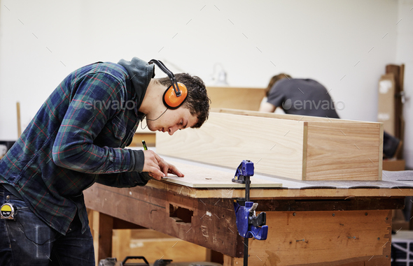 A man marking a piece of wood with a pencil. - Stock Photo - Images