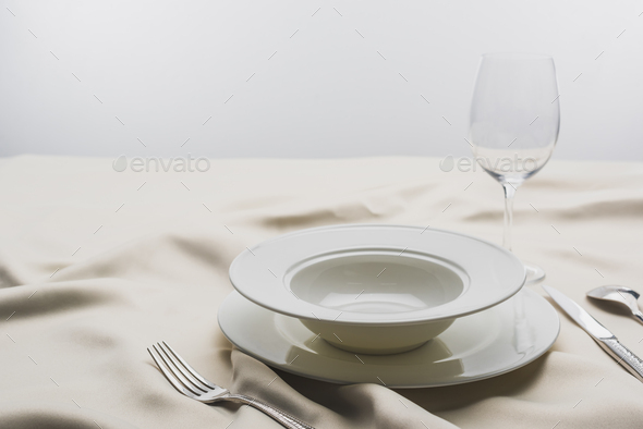 Selective Focus of Plates And Wine Glass on Tablecloth on Grey Background - Stock Photo - Images