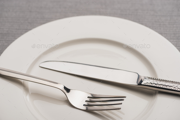 Close up View of Cutlery on Empty Plate on Grey Surface - Stock Photo - Images