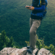 Hiker using smartphone  on forest mountain top cliff edge - PhotoDune Item for Sale