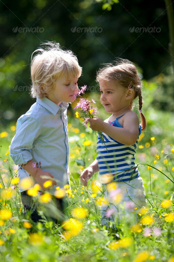 Little Boy And Girl Picking Flowers In The Parc - Stock Photo - Images