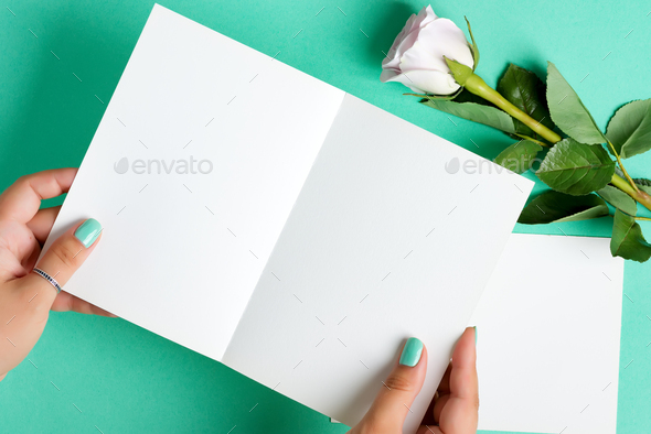 Woman's hands are holding empty mock-up paper sheet for writing letter above pastel turquoise - Stock Photo - Images
