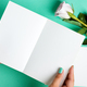 Woman's hands are holding empty mock-up paper sheet for writing letter above pastel turquoise - PhotoDune Item for Sale