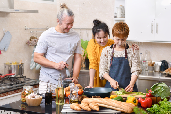 Family cooking in kitchen together - Stock Photo - Images