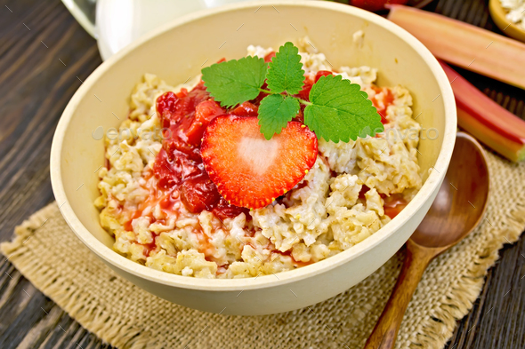 Oatmeal with strawberry-rhubarb sauce on board - Stock Photo - Images