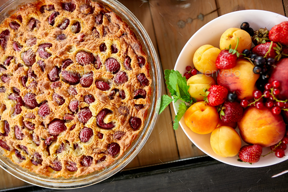 Clafoutis with cherry on a wooden background - Stock Photo - Images