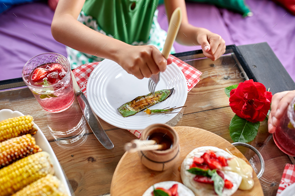 Enjoying dinner child girl eat with knife and fork, dinner table - Stock Photo - Images
