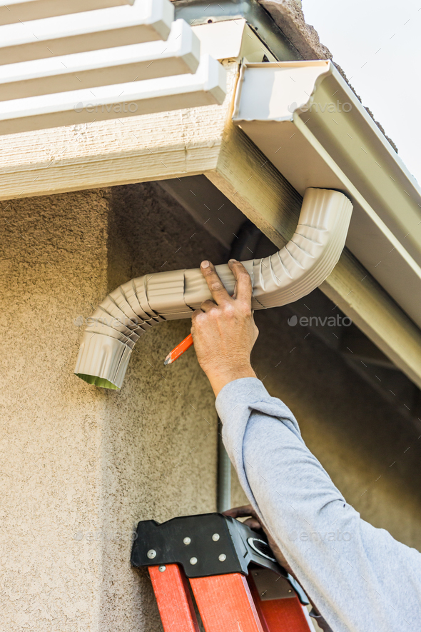 Worker Attaching Aluminum Rain Gutter and Down Spout to Fascia of House - Stock Photo - Images
