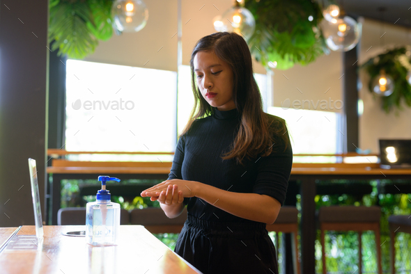 Young beautiful Asian businesswoman using hand sanitizer as proper hygiene etiquette at the coffee - Stock Photo - Images