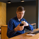 Young handsome businessman with coffee using phone and sitting with distance at the coffee shop - PhotoDune Item for Sale
