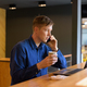 Young handsome businessman with coffee talking on the phone and using laptop while social distancing - PhotoDune Item for Sale