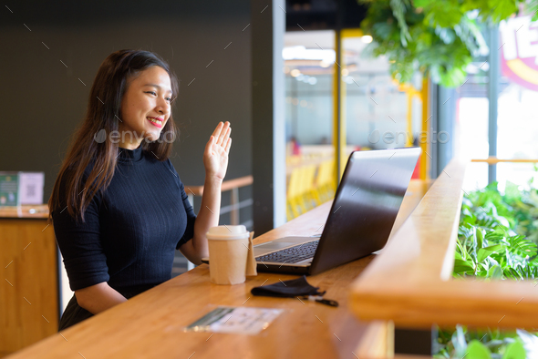 Happy young beautiful Asian businesswoman video calling while sitting with distance inside the - Stock Photo - Images