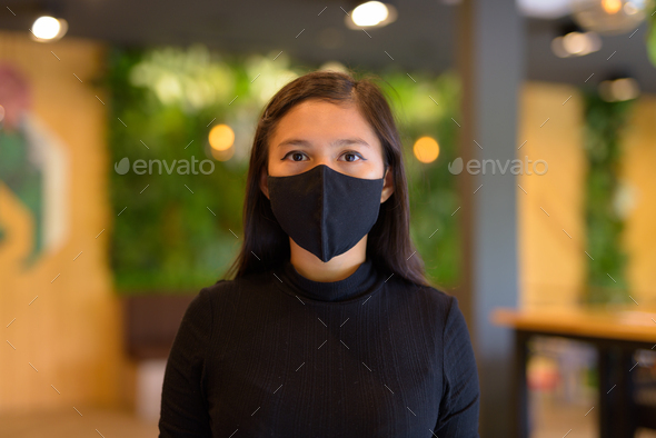 Face of young Asian businesswoman wearing mask and social distancing at the coffee shop - Stock Photo - Images