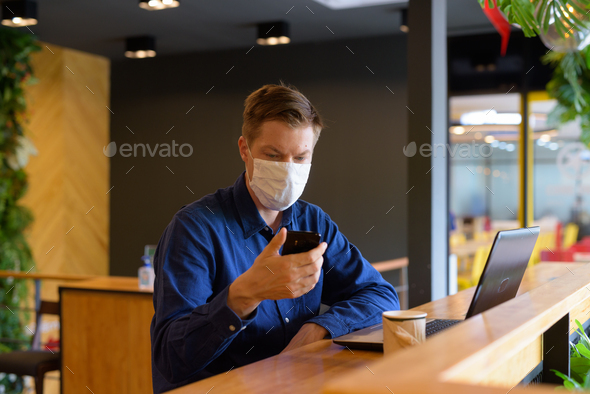 Young businessman with mask using phone and sitting with distance inside the coffee shop - Stock Photo - Images