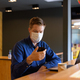 Young businessman with mask using phone and sitting with distance inside the coffee shop - PhotoDune Item for Sale