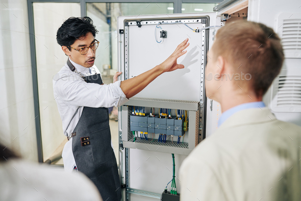 Entrepreneur showing electrical enclosure to inspectors - Stock Photo - Images