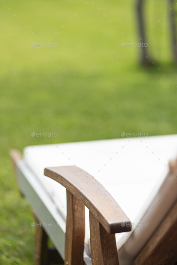 Wooden sunbed on a grass in the private garden - Stock Photo - Images