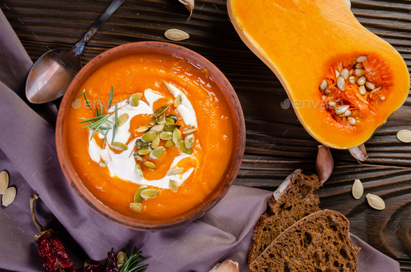 Flat lay view at homemade rustic pumpkin soup with seeds in clay dish - Stock Photo - Images
