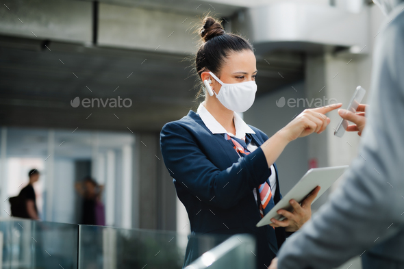 Flight attendant talking to businessman on airport, wearing face mask - Stock Photo - Images
