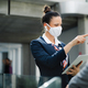 Flight attendant talking to businessman on airport, wearing face mask - PhotoDune Item for Sale