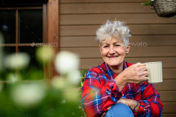 Senior woman with coffee sitting on terrace in summer, resting - Stock Photo - Images