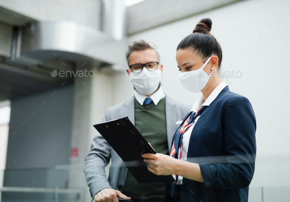 Flight attendant talking to mature businessman on airport, wearing face masks - Stock Photo - Images