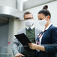 Flight attendant talking to mature businessman on airport, wearing face masks - PhotoDune Item for Sale