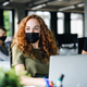 Young woman with face mask back at work in office after lockdown - PhotoDune Item for Sale