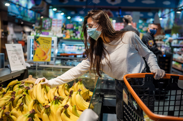 The girl with surgical mask is going to buy bananas - Stock Photo - Images