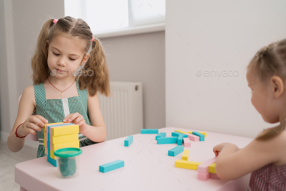 Beautiful caucasian girls playing with wooden multi-colored blocks - Stock Photo - Images
