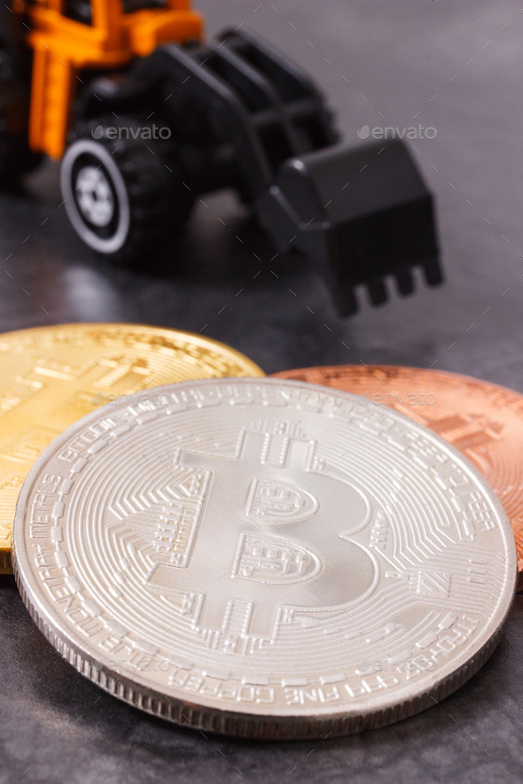 Bitcoins and miniature excavator, symbol of new virtual money and mining cryptocurrency - Stock Photo - Images