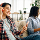 Two cute women in headphones leisures on sofa - PhotoDune Item for Sale