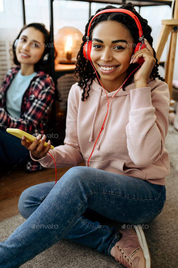 Women in headphones listening to music at home - Stock Photo - Images