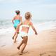 Two positive little girls run along sandy beach - PhotoDune Item for Sale