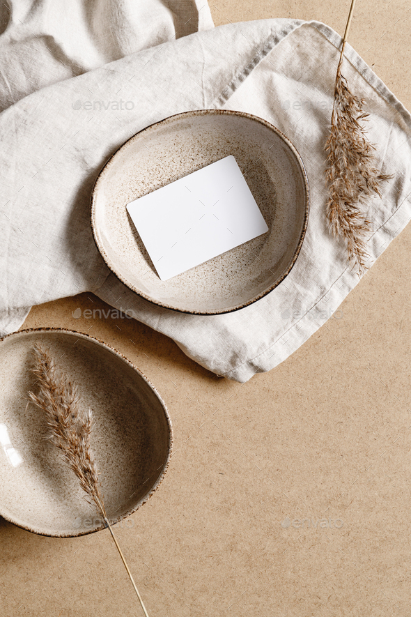Blank paper sheet card in a bowl. Minimalist ceramics set over a linen cloth. - Stock Photo - Images