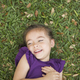 A child lying on her back on the grass. - PhotoDune Item for Sale