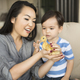 Smiling woman holding a yellow duckling in her hands, her young son watching. - PhotoDune Item for Sale