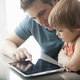 A father and his daughter looking at a digital tablet, using the touch screen. - PhotoDune Item for Sale