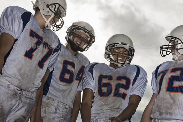 A group of football players, members of a squad, young people in sports uniform and protective helmets, heads and shoulders.